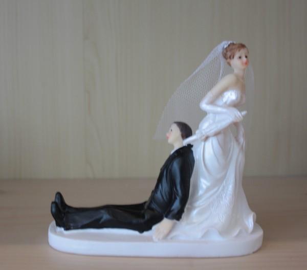 Braut zieht Bräutigam mit schirm